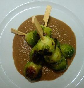 Brochetas de coles de Bruselas con salsa de cebolla caramelizada